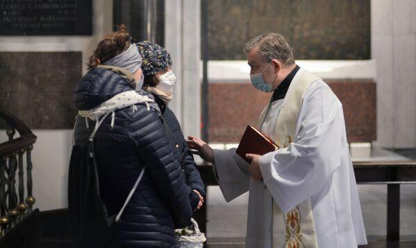 Parafianie rozmawiają z księdzem w kościele w przeddzień świąt wielkanocnych w Warszawie - Sputnik Polska