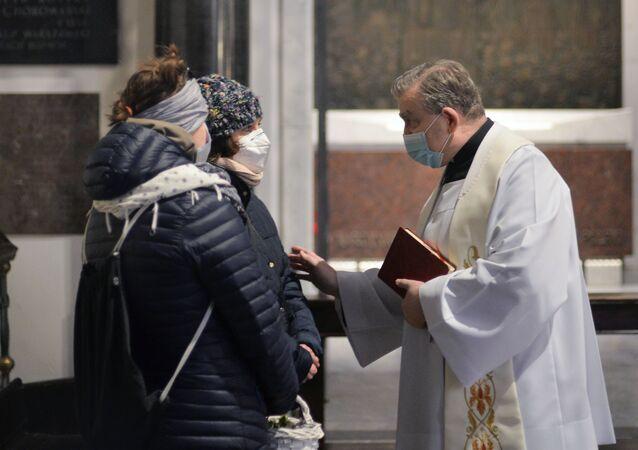 Parafianie rozmawiają z księdzem w kościele w przeddzień świąt wielkanocnych w Warszawie