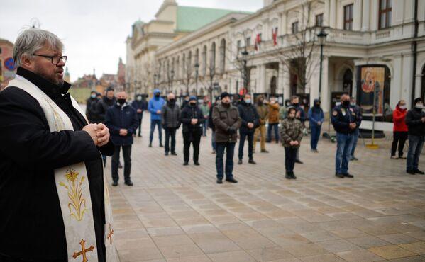 Ksiądz i parafianie podczas nabożeństwa ulicznego w przededniu świąt wielkanocnych w Warszawie - Sputnik Polska
