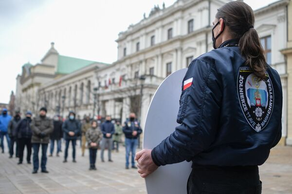Mężczyzna w masce trzyma obraz Matki Boskiej podczas nabożeństwa w Wielką Sobotę w Warszawie - Sputnik Polska