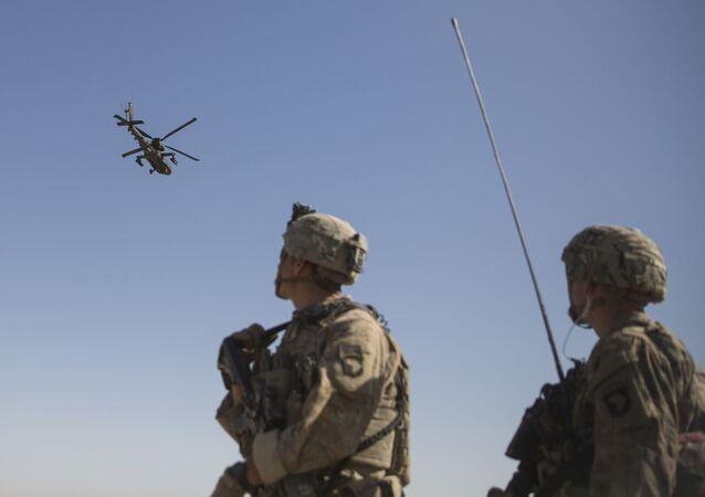 Amerykańscy Marines obserwują helikopter AH-64 Apache na lotnisku Bost w Afganistanie.