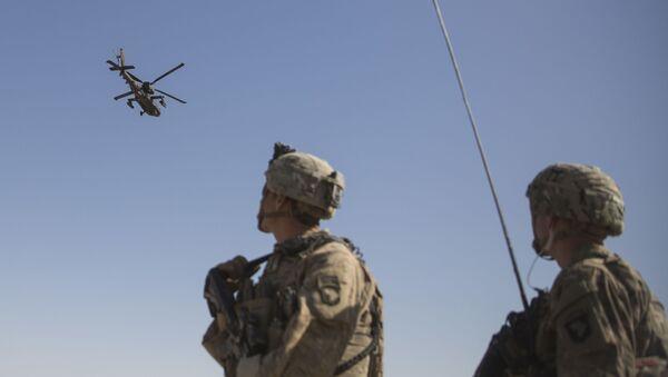 Amerykańscy Marines obserwują helikopter AH-64 Apache na lotnisku Bost w Afganistanie - Sputnik Polska