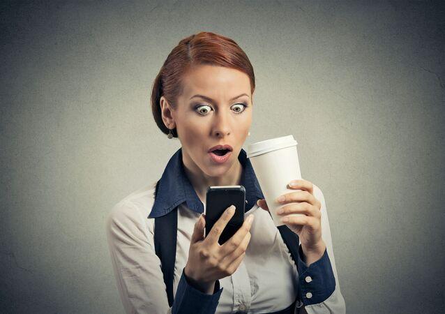 Zdziwiona kobieta ze smartfonem i kawą w rękach
