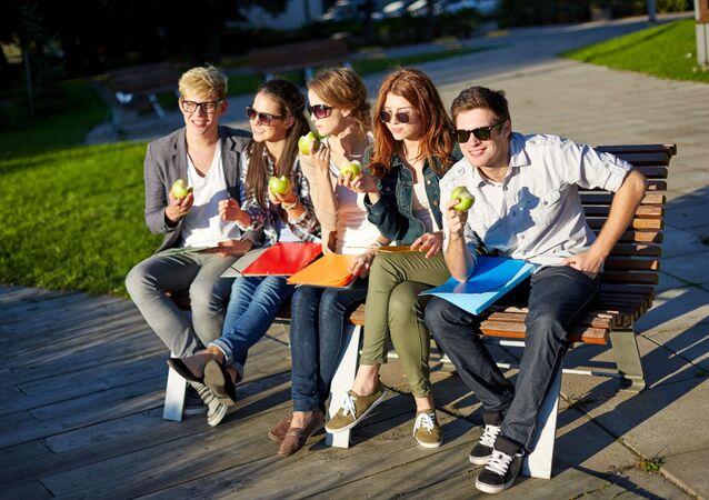 Młodzi ludzie jedzą jabłka na ławeczce w parku.