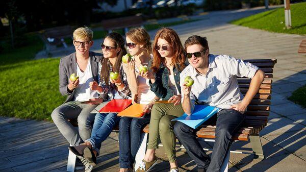 Młodzi ludzie jedzą jabłka na ławeczce w parku. - Sputnik Polska