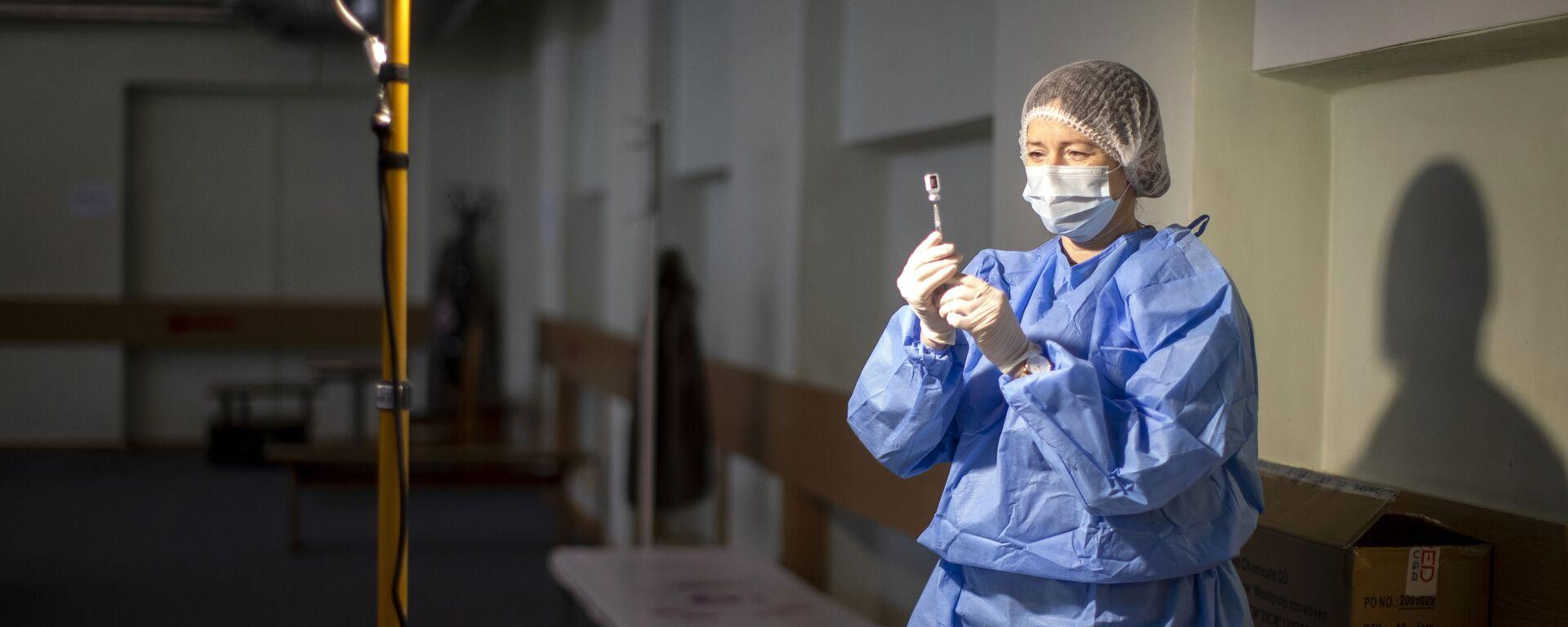 Litewski pracownik medyczny przygotowuje szczepionkę przeciwko koronawirusowi - Sputnik Polska, 1920, 17.07.2021