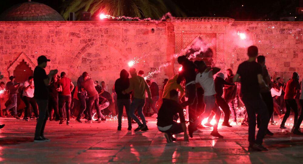 Palestyńczycy reagują jak izraelska policja wystrzeliwuje granaty w dzielnicy Sheikh Jarrah na Starym Mieście w Jerozolimie, 7 maja 2021 r