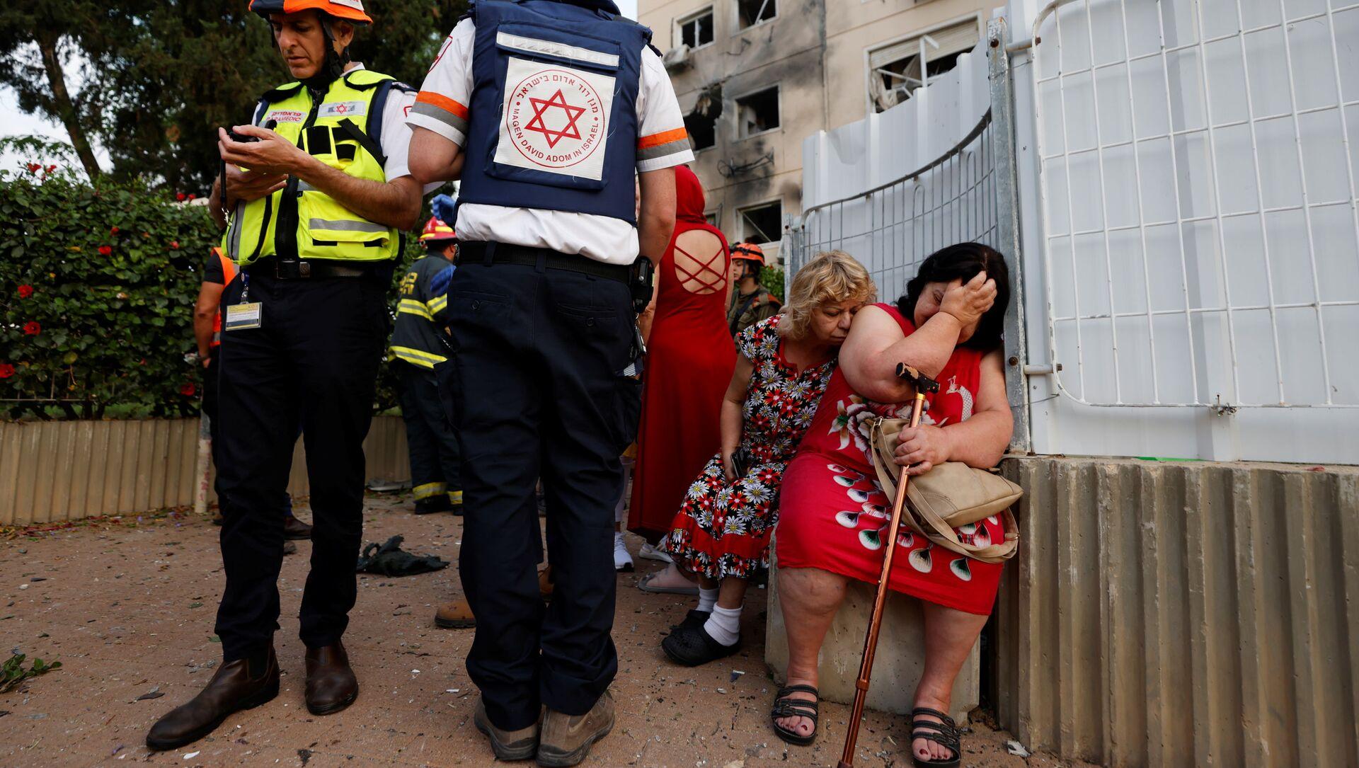 Izraelscy lekarze stoją obok kobiet przed domem uszkodzonym przez pocisk wystrzelony ze Strefy Gazy  - Sputnik Polska, 1920, 11.05.2021