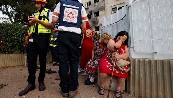 Izraelscy lekarze stoją obok kobiet przed domem uszkodzonym przez pocisk wystrzelony ze Strefy Gazy  - Sputnik Polska