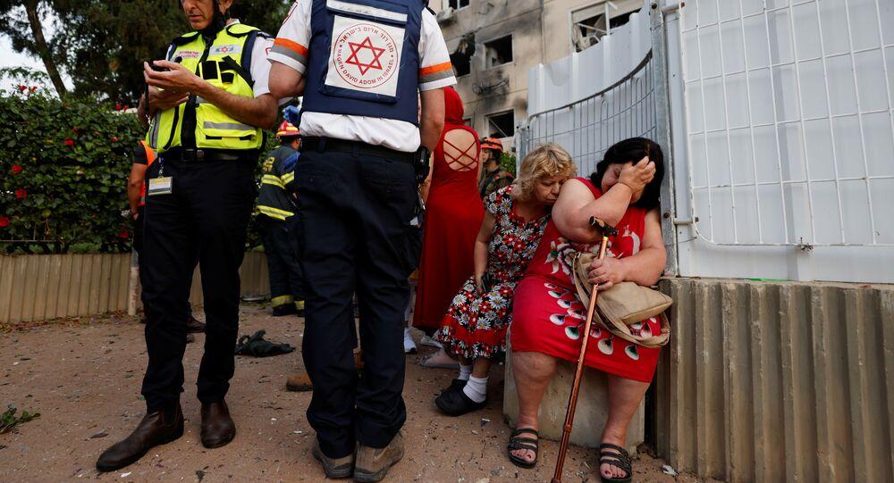 Izraelscy lekarze stoją obok kobiet przed domem uszkodzonym przez pocisk wystrzelony ze Strefy Gazy