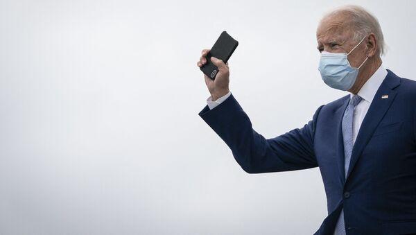 Joe Biden z telefonem w dłoni - Sputnik Polska