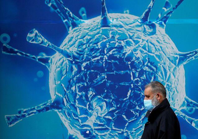 Mężczyzna w masce na tle ilustracji wirusa.