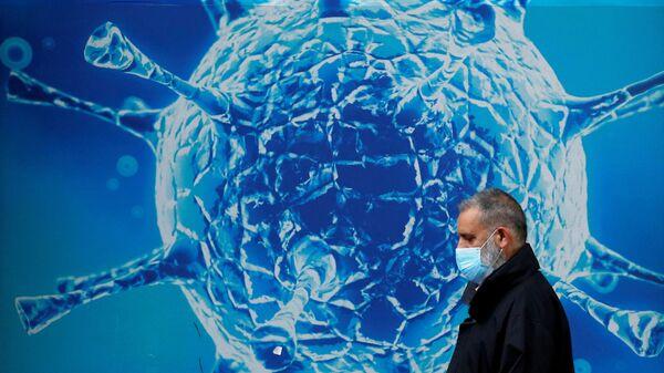 Mężczyzna w masce na tle ilustracji wirusa - Sputnik Polska