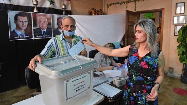 Kobieta głosuje w wyborach prezydenckich w Syrii w jednym z lokali wyborczych w Damaszku - Sputnik Polska