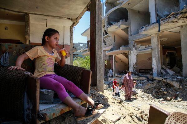 Dziewczyna pije sok w zniszczonym domu w północno-wschodniej Strefie Gazy  - Sputnik Polska