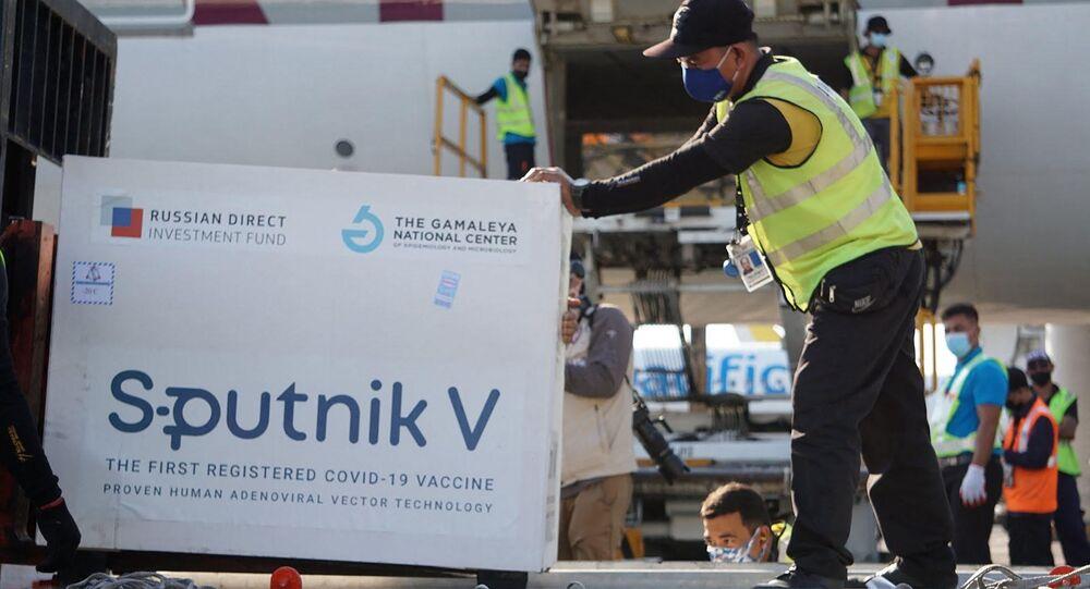 """Pracownicy rozładowujący pierwszą partię rosyjskiej szczepionki przeciwko koronawirusowi """"Sputnik V"""" na lotnisku w Manili"""