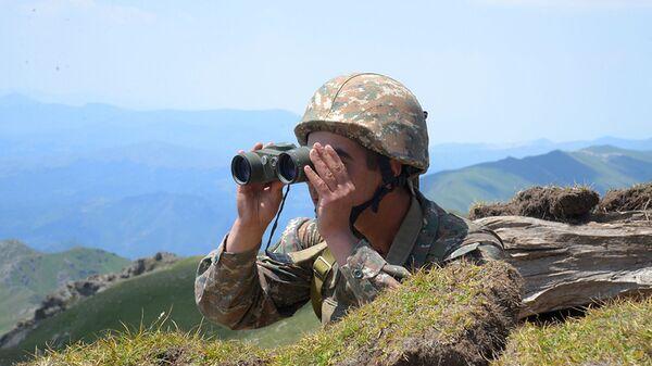 Armeński żołnierz patrzy przez lornetkę na swoje pozycji na linii frontu w prowincji Tawusz, Armenia - Sputnik Polska