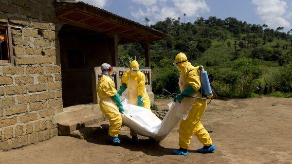 Personel Gwinejskiego Czerwonego Krzyża w kombinezonach ochronnych niesie zwłoki ofiary wirusa Ebola. - Sputnik Polska