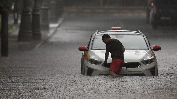 Водитель такси возле машины на затопленной улице в Москве - Sputnik Polska