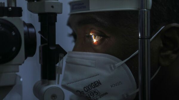Врач проверяет пациента на симптомы мукормикоза с помощью щелевой лампы в больнице в Мумбаи, Индия - Sputnik Polska