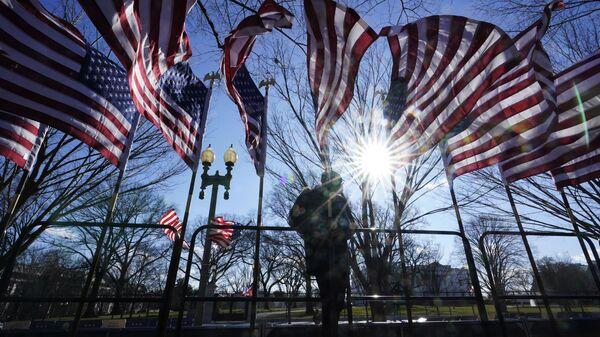 Рабочий устанавливает флаги к церемонии инаугурации избранного президента Джо Байдена в Вашингтоне - Sputnik Polska