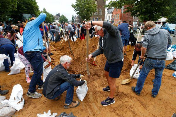 Ludzie napełniają worki z piaskiem po ulewnych deszczach w Erftstadt w Niemczech, 16 lipca 2021 r. - Sputnik Polska