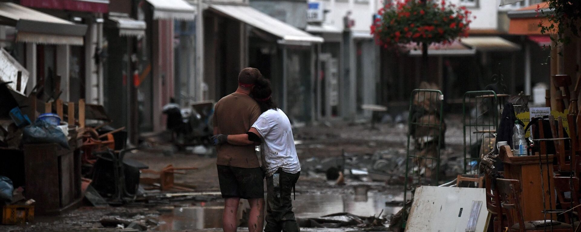 Пара обнимаются, стоя среди обломков, в городе Бад-Нойенар-Арвайлер, Германия  - Sputnik Polska, 1920, 18.07.2021
