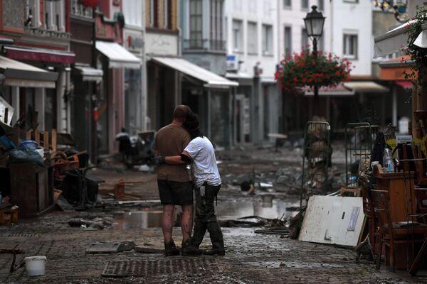 Para obejmuje się, stojąc wśród gruzu pozostawionego przez wody powodziowe na ulicy w mieście Bad Neuenahr-Ahrweiler 15 lipca 2021 r. - - Sputnik Polska