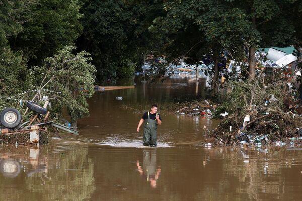 Mężczyzna przechodzi przez wodę na obszarze dotkniętym powodzią po ulewnych deszczach w Bad Neuenahr-Ahrweiler, Niemcy, 15 lipca 2021 r. - Sputnik Polska