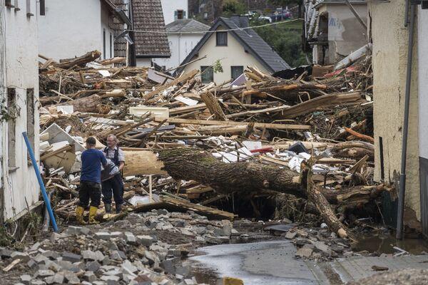 Mężczyzni obok gruzu i domów zniszczonych przez powódź w Schuld koło Bad Neuenahr w zachodnich Niemczech, 15 lipca 2021 r.  - Sputnik Polska