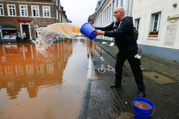 Andreas Schloemer opróżnia wiadro wody po ulewnych deszczach w Erftstadt w Niemczech, 16 lipca 2021 r. - Sputnik Polska