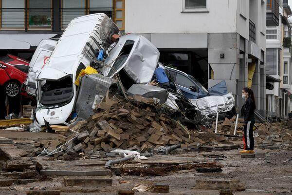 Kobieta stoi obok samochodów i gruzu spiętrzonego na ulicy po tym, jak powodzie spowodowały poważne szkody w Bad Neuenahr-Ahrweiler w zachodnich Niemczech, 16 lipca 2021 r.  - Sputnik Polska