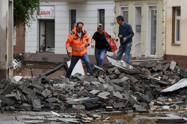 Ludzie wspinają się po gruzach spiętrzonych na ulicy po tym, jak powodzie spowodowały poważne szkody w Bad Neuenahr-Ahrweiler w zachodnich Niemczech, 16 lipca 2021 r. - Sputnik Polska