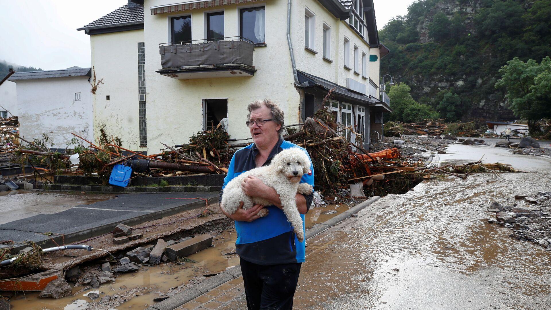 Мужчина с собакой на затопленной и заваленной ветками улице в Шульде, Германия, 15 июля 2021 года. - Sputnik Polska, 1920, 18.07.2021