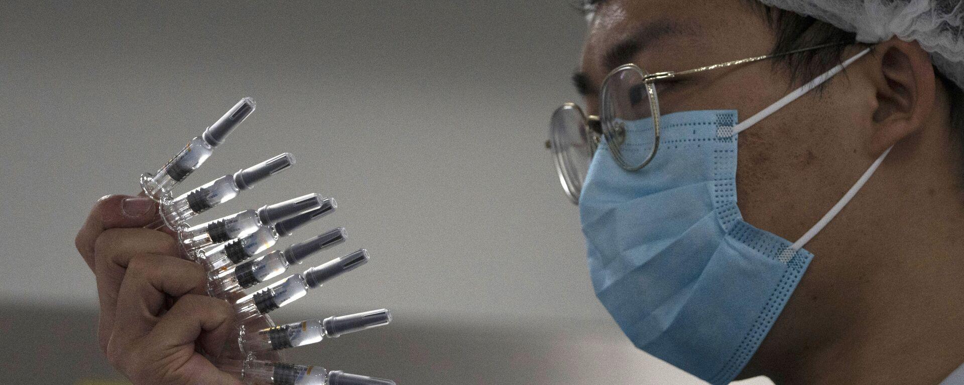 Pracownik kontroluje strzykawki zawierające szczepionkę przeciwko SARS-CoV-2 w fabryce w Pekinie - Sputnik Polska, 1920, 17.07.2021