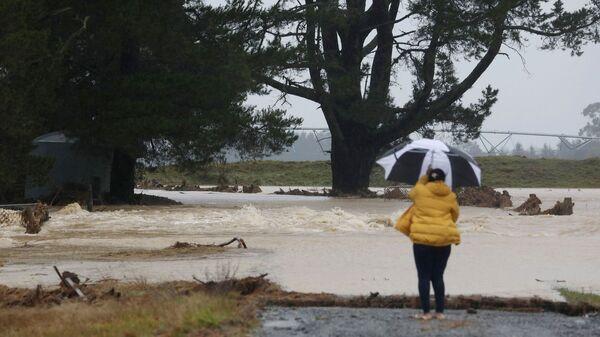 Женщина смотрит на сельхозугодья, затопленные вышедшей из берегов рекой Хокинс в районе Гриндейл провинции Кентербери, Новая Зеландия - Sputnik Polska