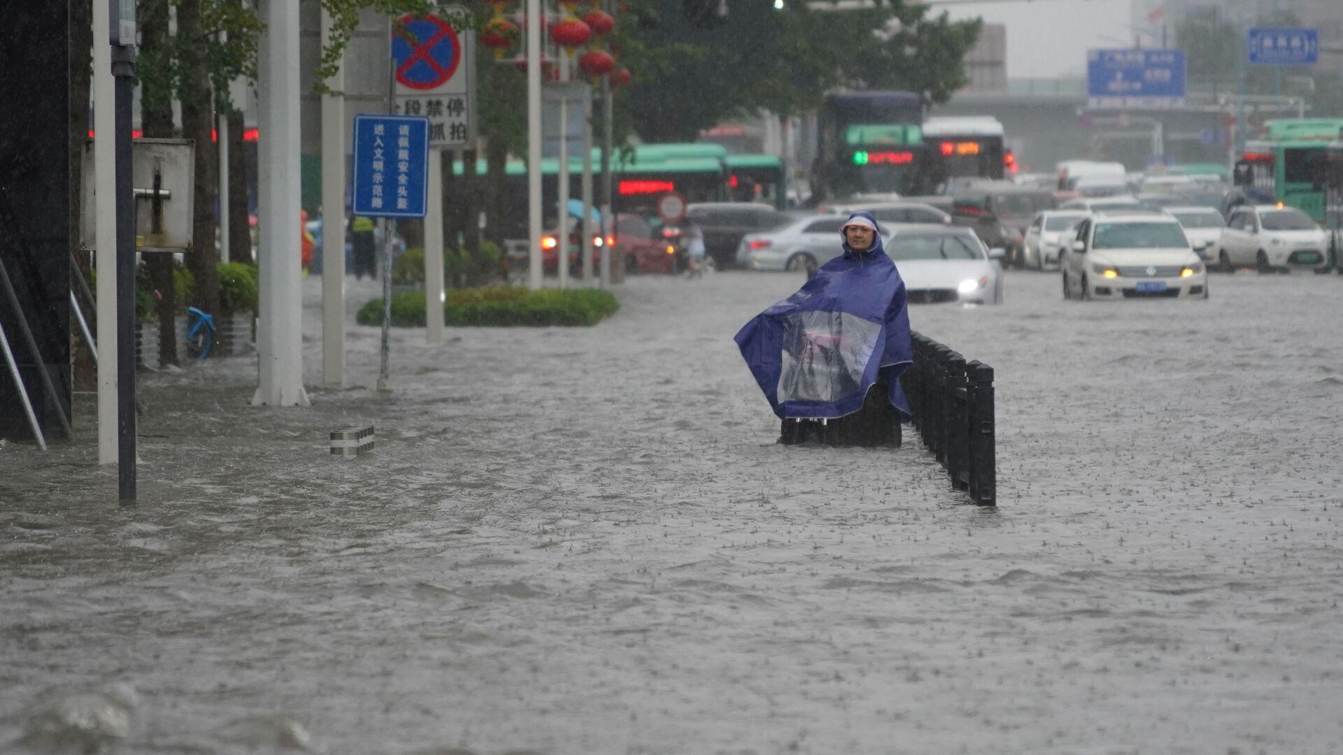 Mieszkaniec na zalanej ulicy w chińskiej prowincji Henan - Sputnik Polska, 1920, 22.07.2021