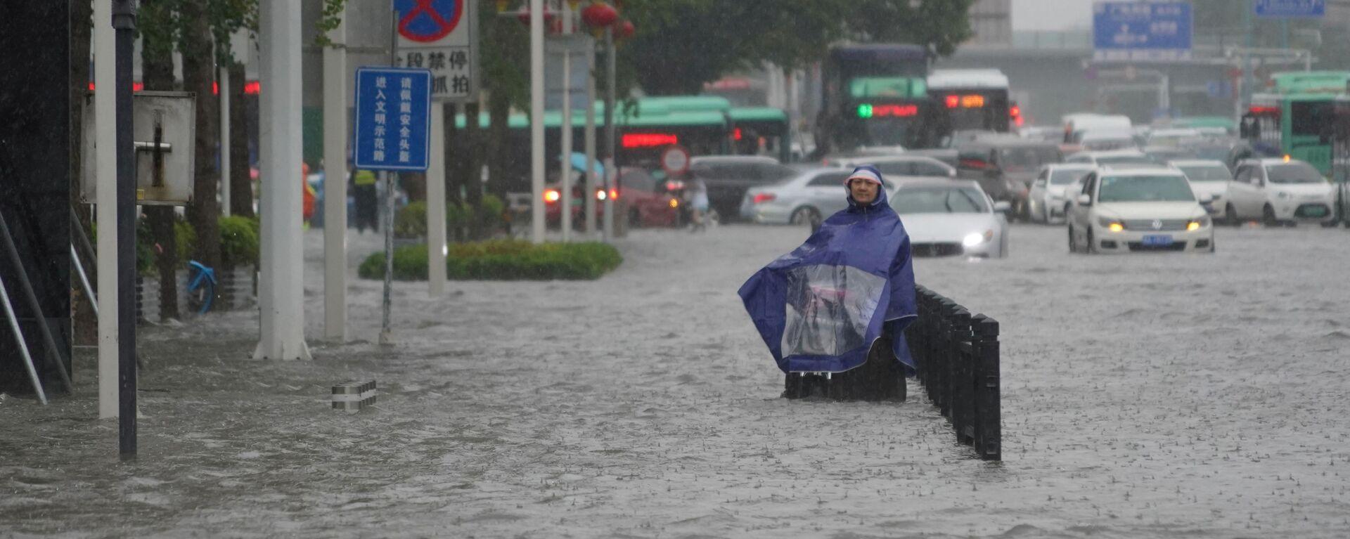 Mieszkaniec na zalanej ulicy w chińskiej prowincji Henan - Sputnik Polska, 1920, 21.07.2021