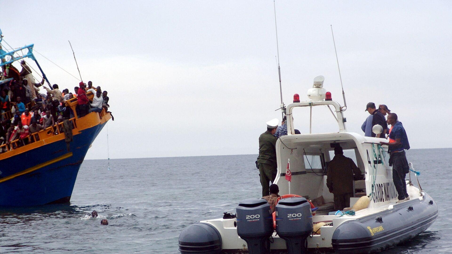Tunezyjska straż przybrzeżna z uratowanymi migrantami z Libii u wybrzeży Tunezji - Sputnik Polska, 1920, 22.07.2021