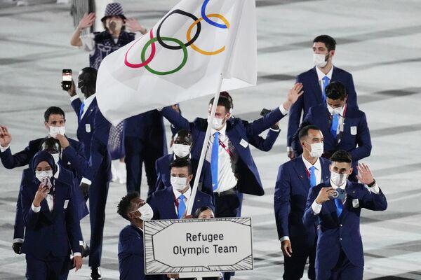 Yusra Mardini i Tachlowini Gabriyesos z Reprezentacji Olimpijskiej niosą flagę olimpijską podczas ceremonii otwarcia na Stadionie Olimpijskim na Letnich Igrzyskach Olimpijskich 2020. - Sputnik Polska