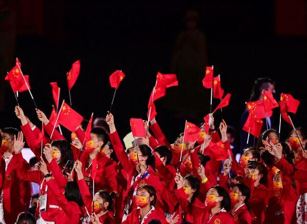 Członkowie chińskiej reprezentacji machają flagami, gdy wchodzą na Stadion Olimpijski podczas ceremonii otwarcia Igrzysk Olimpijskich Tokio 2020. - Sputnik Polska