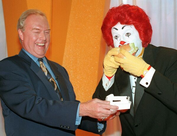 Były dyrektor McDonald's Corporation Michael R. Quinlan z clownem Ronaldem McDonaldem jedzą burgera, 1996 rok. - Sputnik Polska