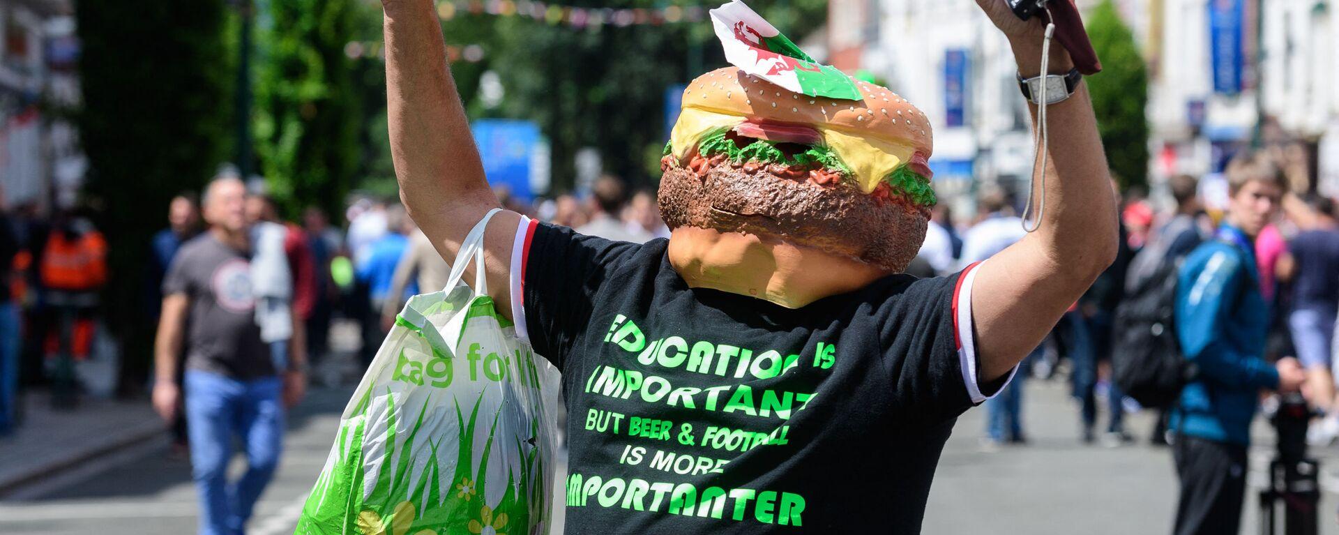 Мужчина в маске гамбургера направляется к стадиону в центре города Ланс-ин-Ланс, Франция  - Sputnik Polska, 1920, 05.08.2021