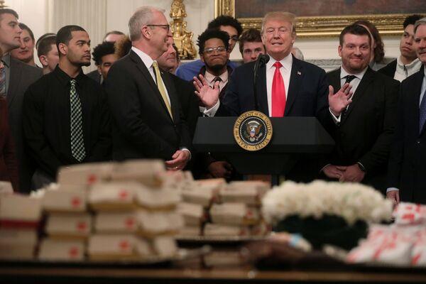 Donald Trump stoi przed stołem z hamburgerami. - Sputnik Polska