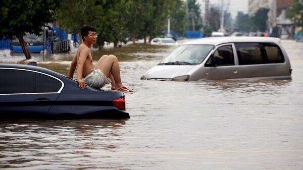 Мужчина сидит на застрявшем автомобиле на затопленной дороге после проливного дождя в Чжэнчжоу, провинция Хэнань, Китай - Sputnik Polska
