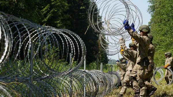 Солдаты литовской армии устанавливают забор из колючей проволоки на границе с Белоруссией в городе Друскининкай  - Sputnik Polska