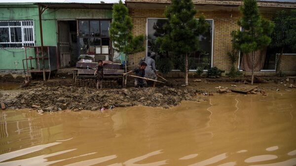 Сельские жители расчищают лопатами грязь грязь на обочине дороги после наводнения в Афганистане - Sputnik Polska