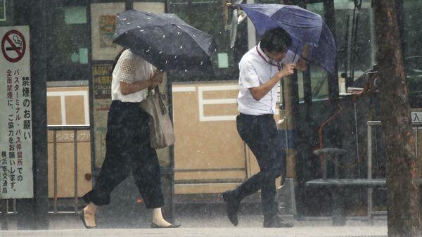 Люди со сломанными зонтами на одной из улиц Токио во время тайфуна Джеба - Sputnik Polska
