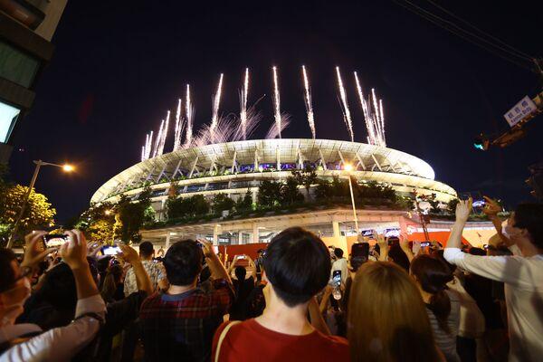 Ceremonia zamknięcia Igrzysk Olimpijskich w Tokio 2020 – Ludzie na zewnątrz stadionu oglądają fajerwerki podczas ceremonii zamknięcia - Sputnik Polska