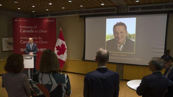 Фотография обвиняемого в шпионаже канадца Майкла Спэйвора на экране в посольстве Канады в Китае  - Sputnik Polska